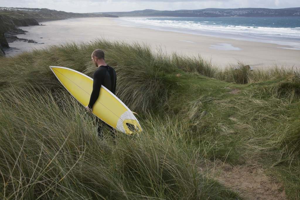 Surfer at Gwithian beach, St ives bay, Cornwall