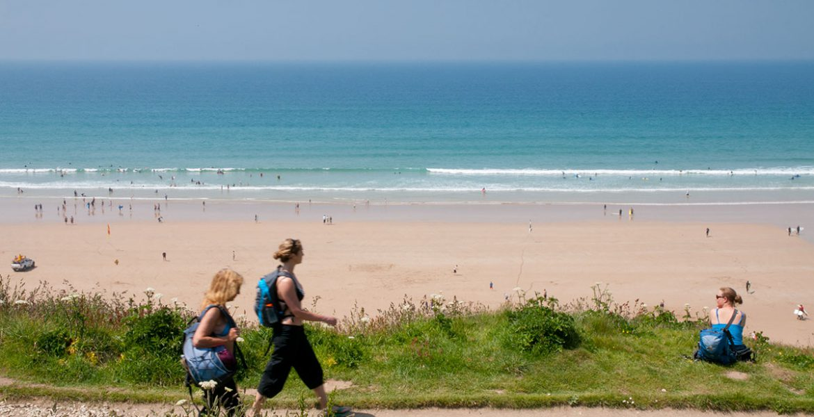 Holidaymakers at beach near holiday accommodation in Newquay by Forever Cornwall