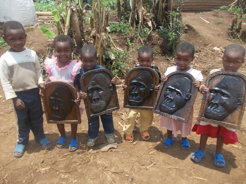 Kindergarten Pupils Holding Wooden Gorilla Portraits Carved By Former Poachers